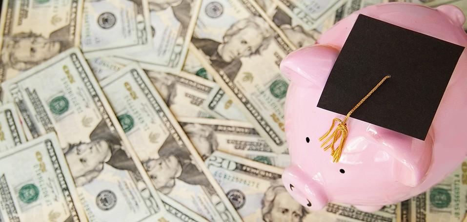 piggy bank with graduation cap on money